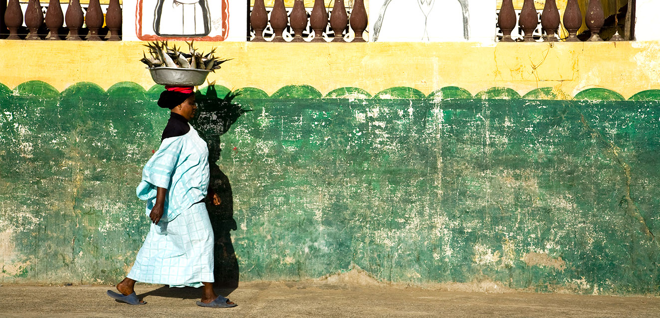 Senegalese woman walking with a large bowl of fresh fish atop her head.
