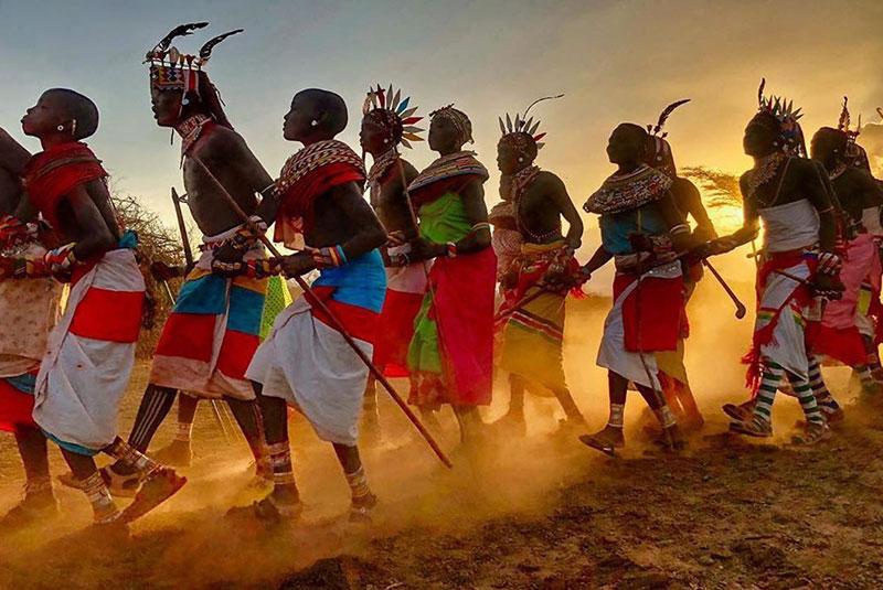 Samburu warriors dancing in golden light, Kenya.
