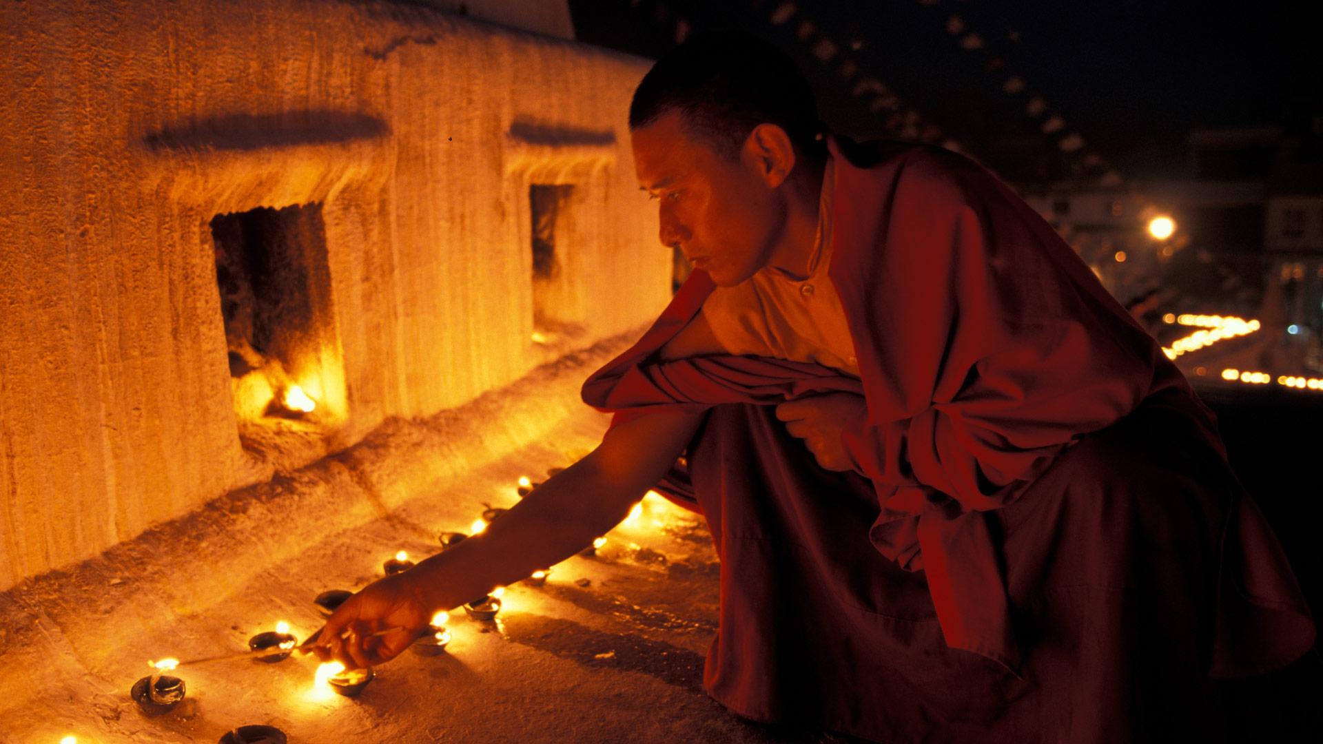 Monk lighting butter lamps at Boudnath, Kathmandu Nepal.