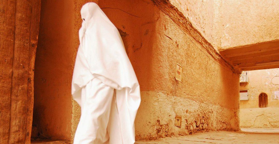Woman walking through narrow streets of Ghardaia, Algeria