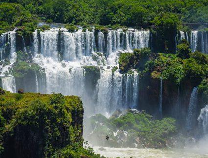 Water cascades down through rain forest vegetation at Iguaza Falls, Argentina