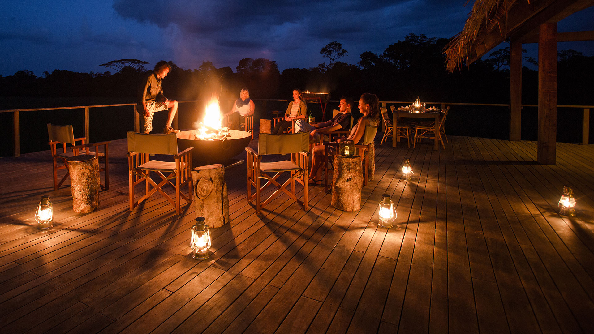 Guests on the deck of Mboko Camp at night, Odzala-Kokoua National Park, Congo