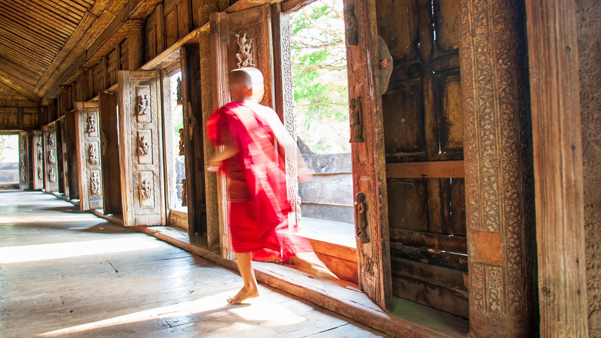 Monk runs down hallway in Mandalay, Myanmar