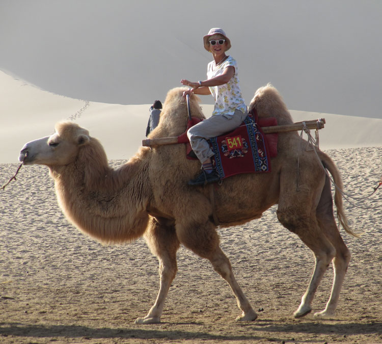 GeoEx guide Tese Wintz Neighbor riding a camel in the desert.