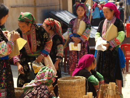 Women in tribal dress gather at a market in Ha Giang Province, Vietnam