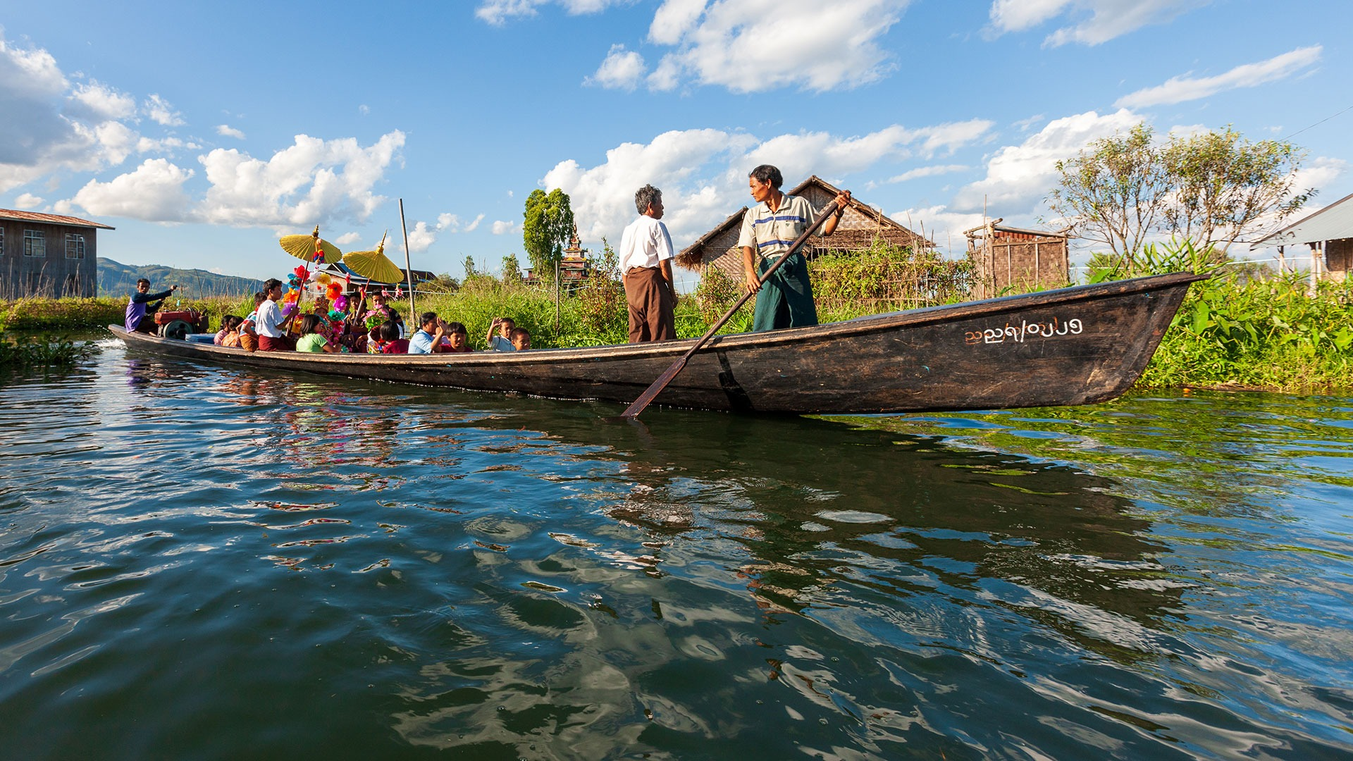 Locals travel the waters on Inle Lake by longtail boat, Myanmar