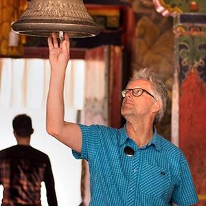 GeoEx trek leader Bart Jordans ringing a bell in Tibet