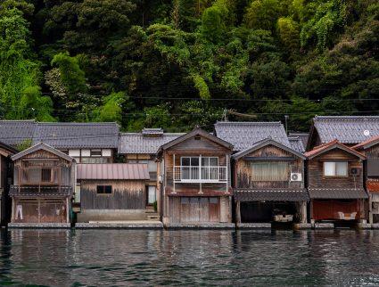 Traditional funaya residences set against lush greenery in Ine, Japan