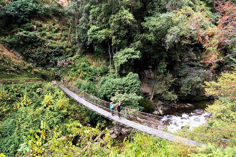 Hikers crossing a bridge on the Hidden Highlands trek in Bhutan