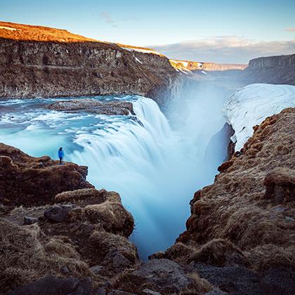 A hiker admiring the rushing waters Gullfoss Falls, Iceland