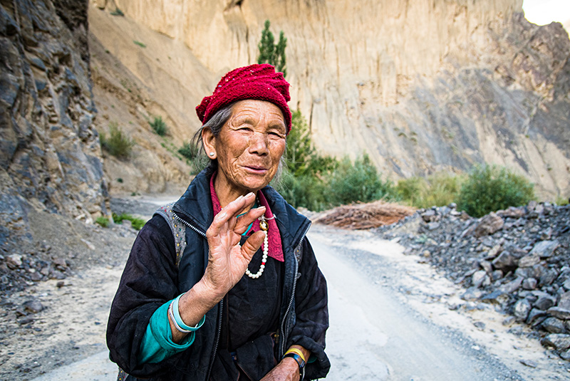 A woman shares a greeting on Mangyu Gorge road in Ladakh, India
