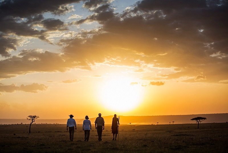 A couple on a sunset walking safari in the Masai Mara, Kenya
