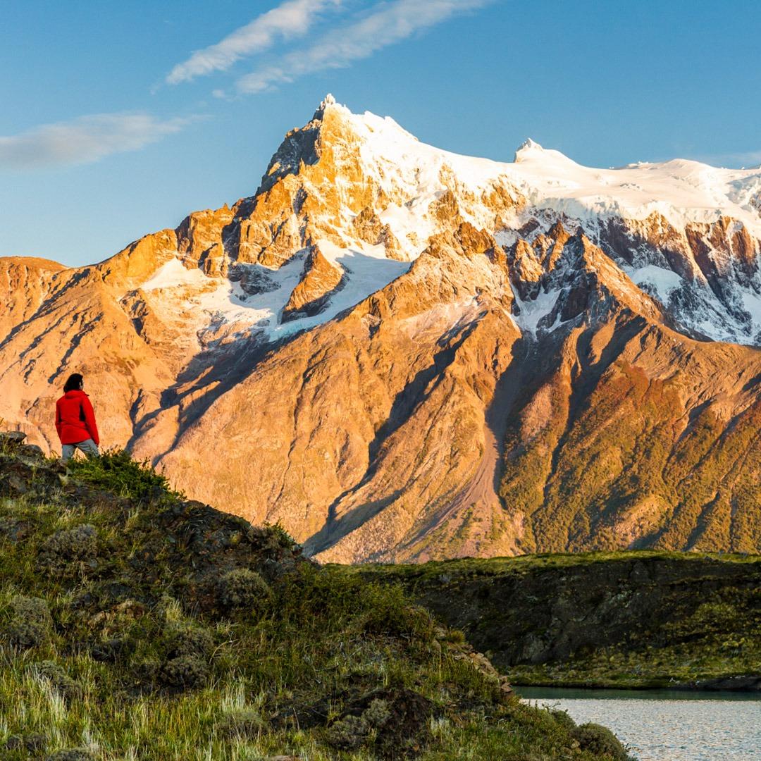 A hiker admires sunrise on Cerro Paine Grande, Torres del Paine, Chile