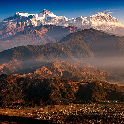 Snowcapped Himalayan peaks tower above the town of Pokhara, Nepal