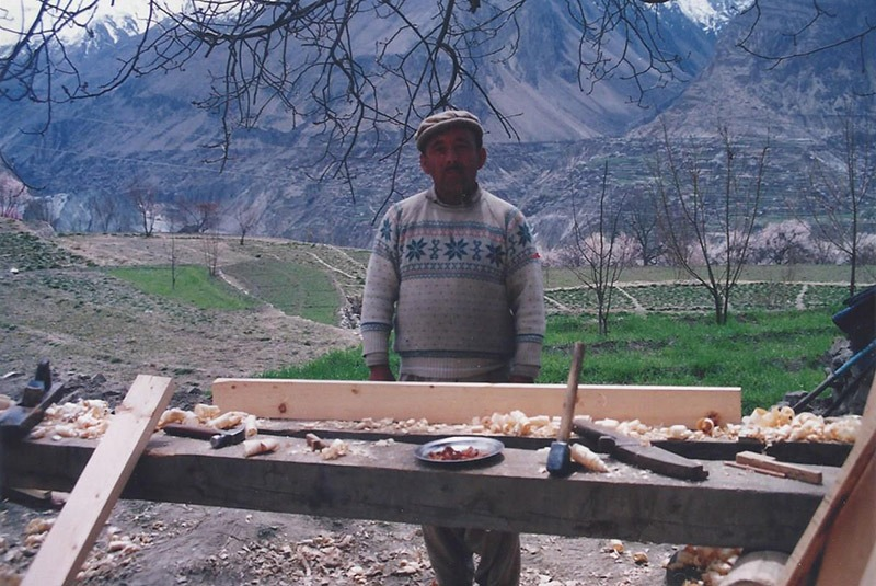 A carpenter works on a door outside of a home in Hunza, Pakistan