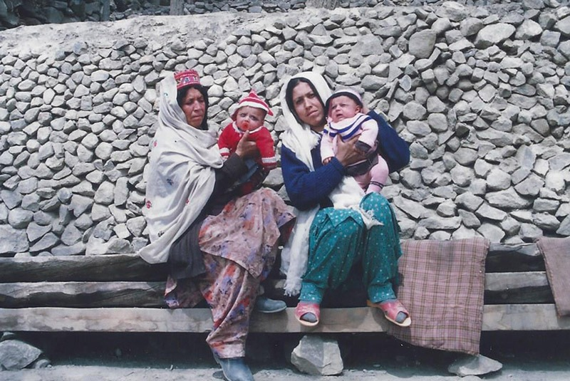 Two women with twin babies outside a home in Hunza, Pakistan