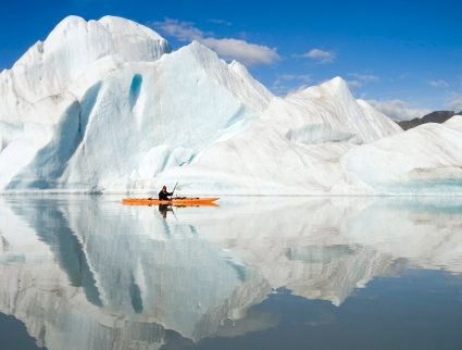 A kayaker paddles past an iceberg in the fjords of Alaska
