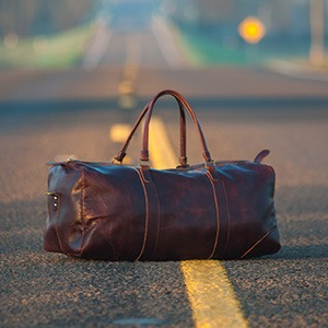 A duffle bag lies in the middle of a road